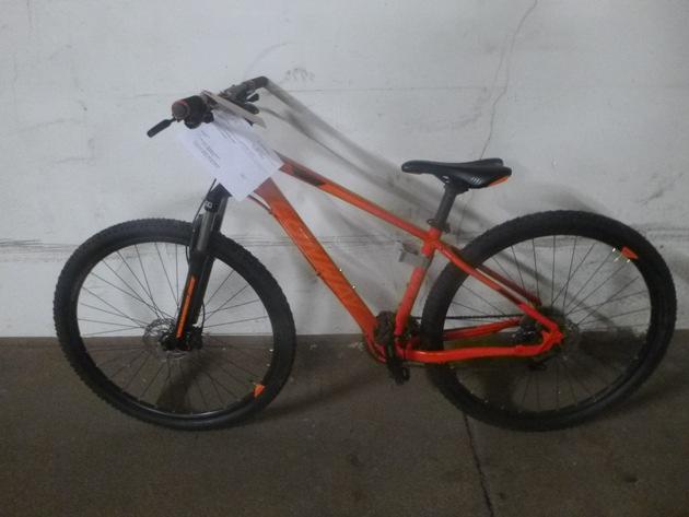 orangefarbenes Mountainbike vor weißer Wand