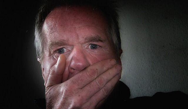 Mann  um die 60 schlägt sich erschrocken die Hand vor den Mund.