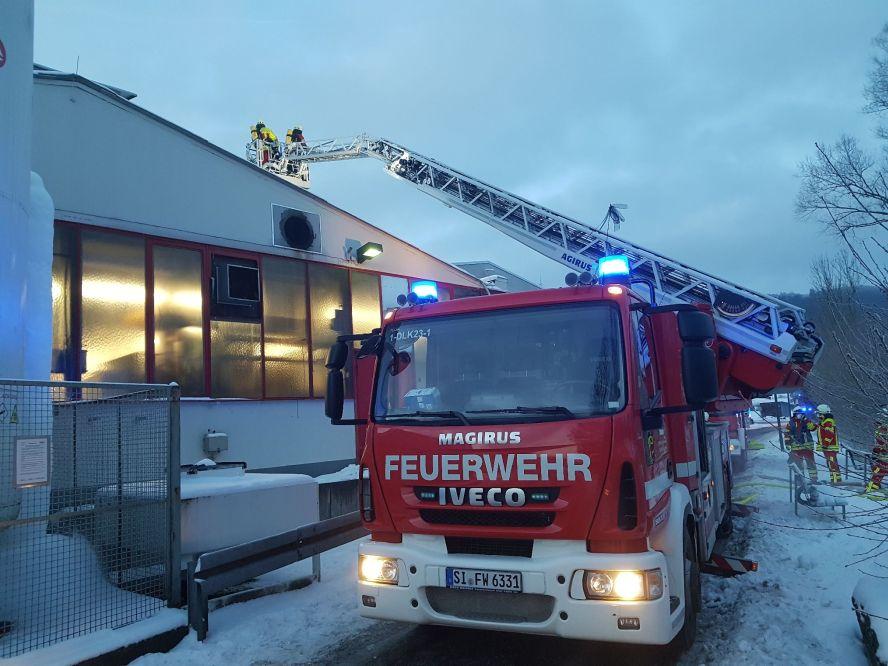 Feuerwehrleute beim Löschen in einem Betrieb (von außen)