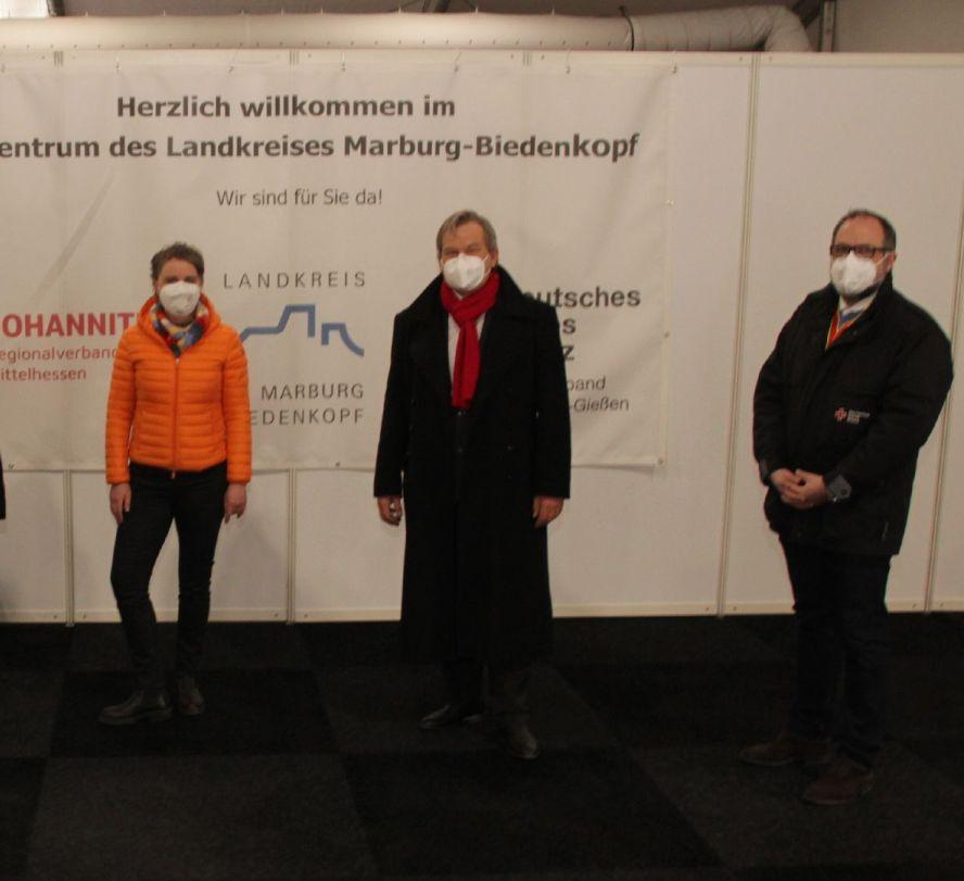 3 Maskierte vor dem Schild des Impfzentrums Marburg