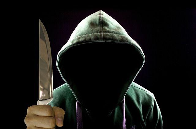 Räuber mit Kapuzenpulli droht mit erhobenem Messer