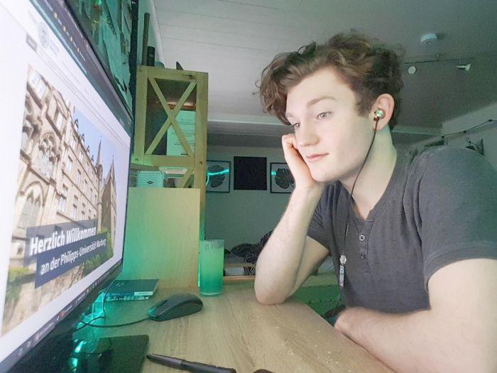 Schüler sitzt im T-Shirt vor dem Rechner