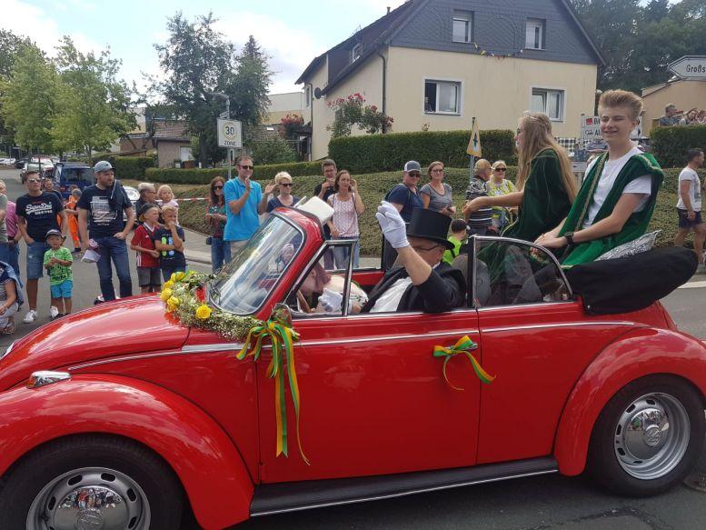 Roter VW Käfer mit dem Prinzenpaar vor Zuschauern