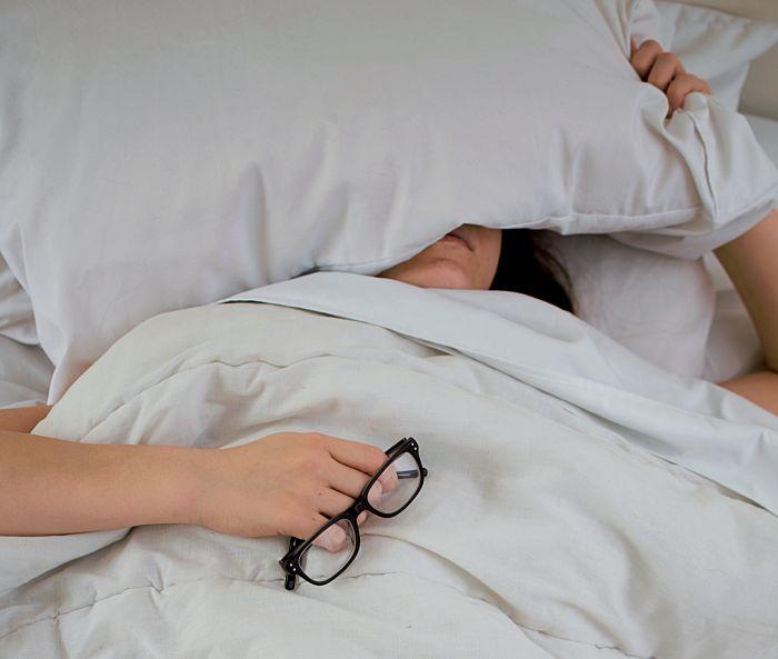 Frau im Bett hält sich Kissen übers GEsicht