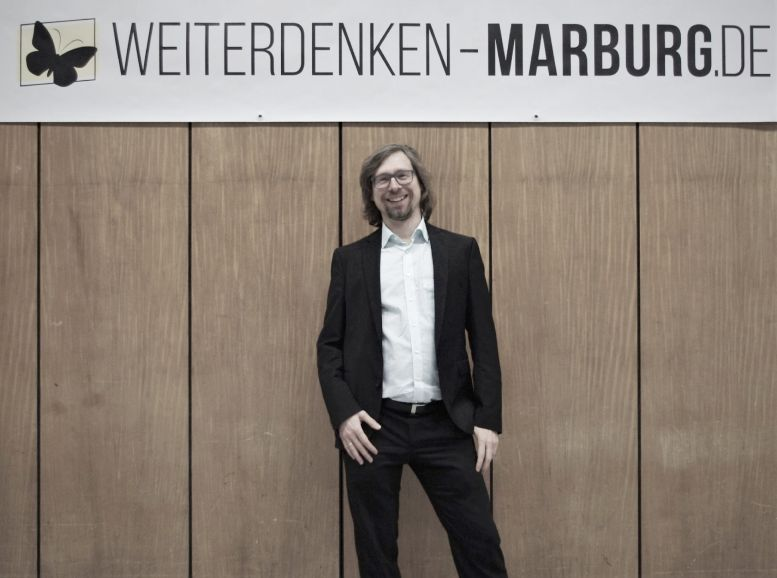 """Mann im Anzug vor einer Wand, darüber Plakat """"Weiterdenken - Marburg.de"""""""