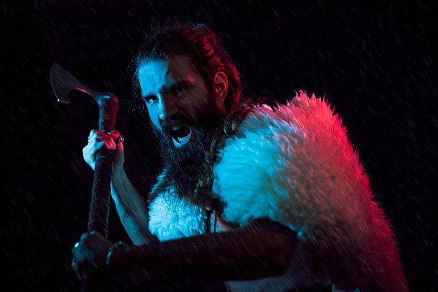 Mann mit Bart in Drohgebärde mit Axt in der Hand.