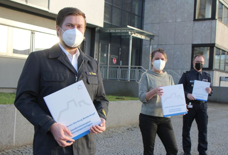 3 Maskierte mit Unterlagen