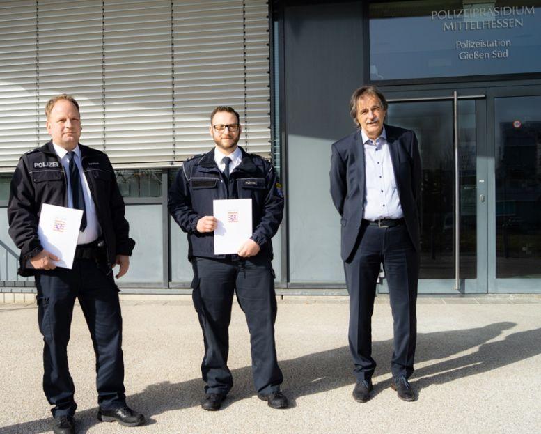 2 Polizisten mit Urkunden und ein Anzugträger vor dem Präsidium