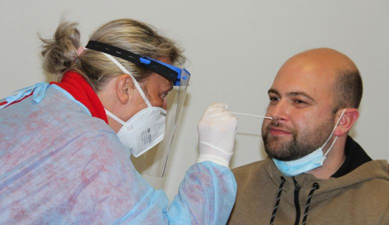 Frau in Schutzkleidung testet Mann auf Corona (Nasenabstrich)