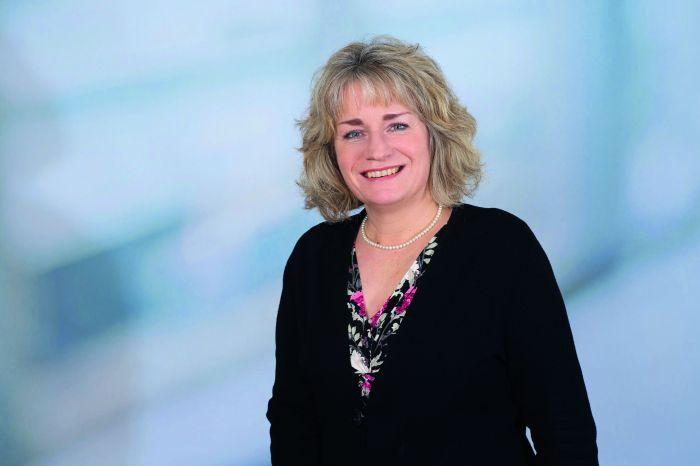 Blonde Frau um die 50 vor blauem Hintergrund