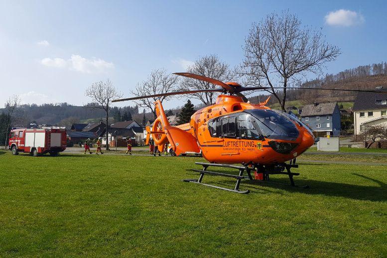 orangefarbener Hubschrauber auf einer Wiese, dahinter Feuerwehr