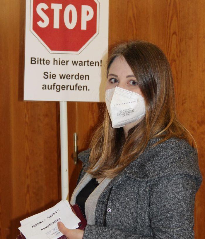 Frau mit Maske wartet vor geschlossener Tür