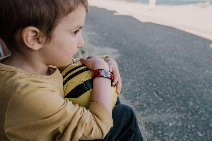 Kind sitz mit Ball am Straßenrand.
