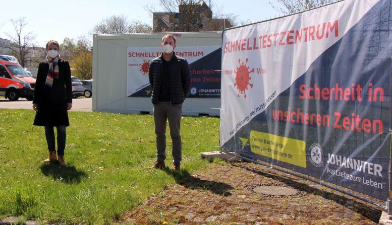 2 Maskierte vor dem Container der das Schnelltest-Zentrum beherbergt.
