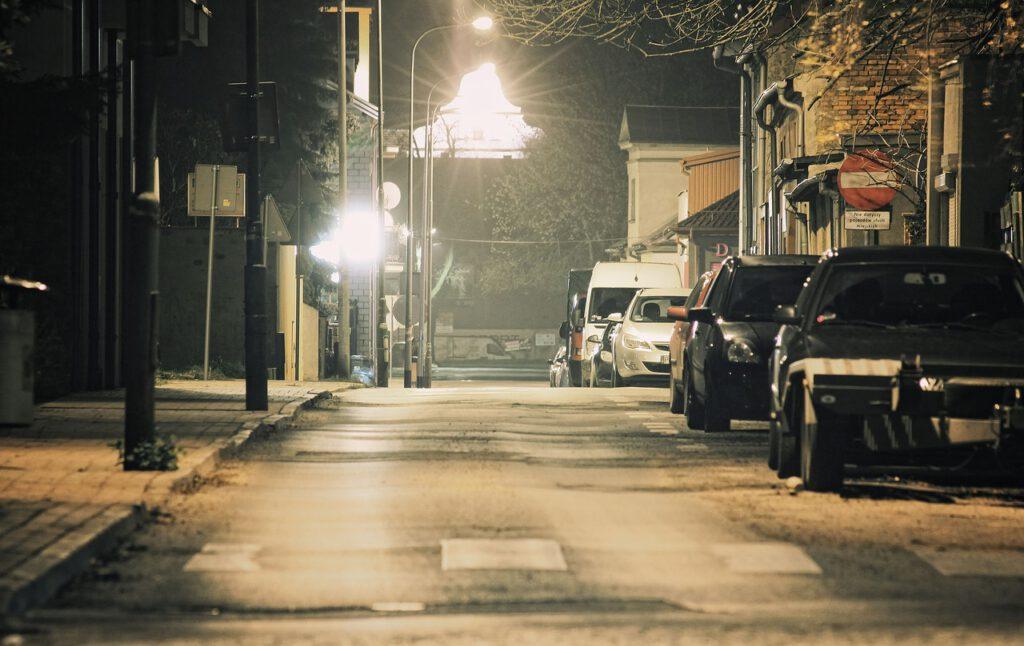 Leere Straße, nächtlich beleuchtet. Parkende Autos.