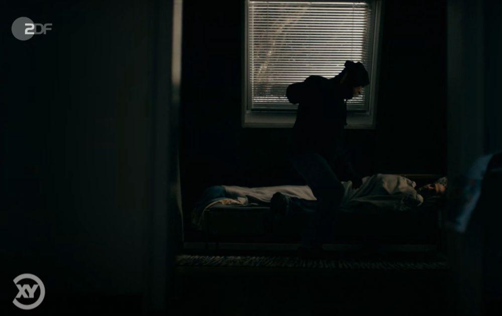 in einem dunklen Zimmer eine Gestalt (Einbrecher) und ein schlafendes Opfer