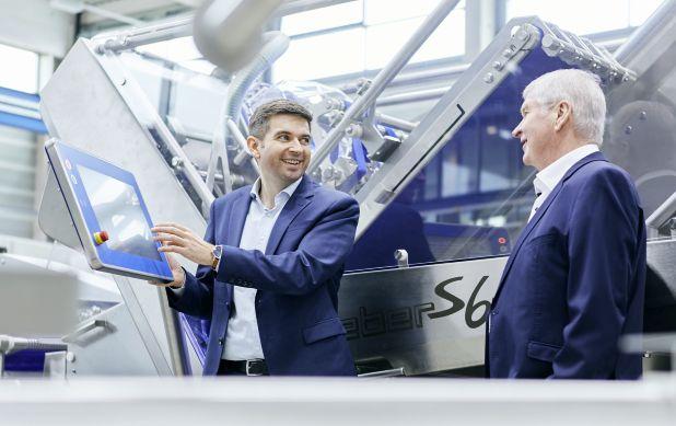 2 Typen in Anzügen an einer großen Maschine