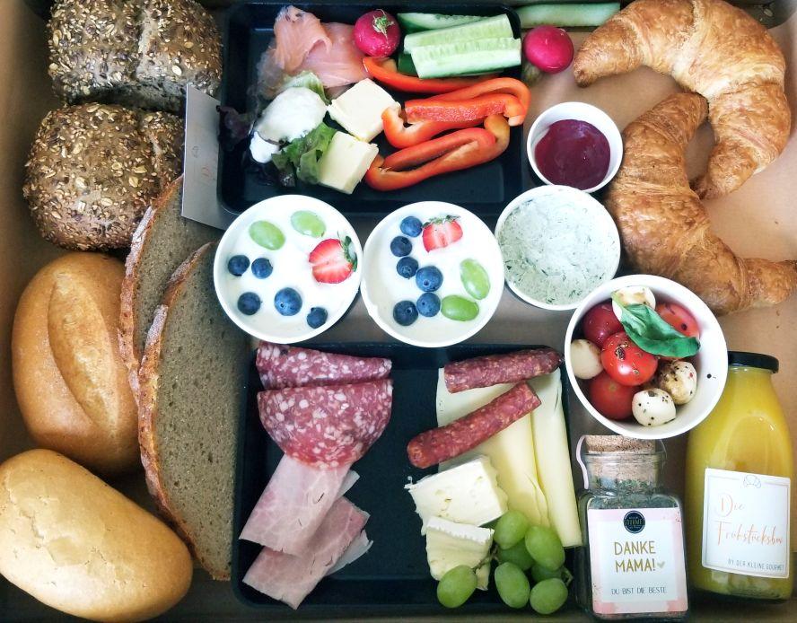 Box mit Brot, Croissants, Dips, Saft und mehr.