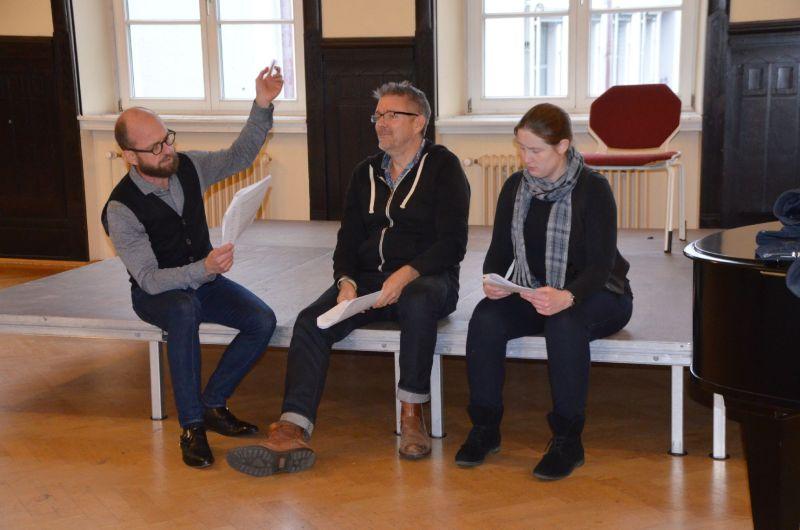 drei Leute sitzend auf einer provisorischen Bühne beim Casting