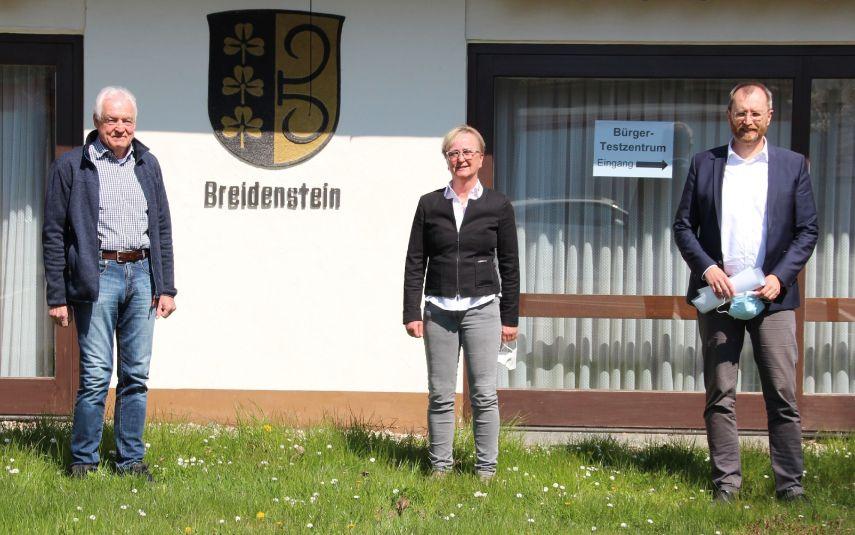 """3 Gestalten vor einem Gebäude mit Stadtwappen """"Breidenstein"""""""