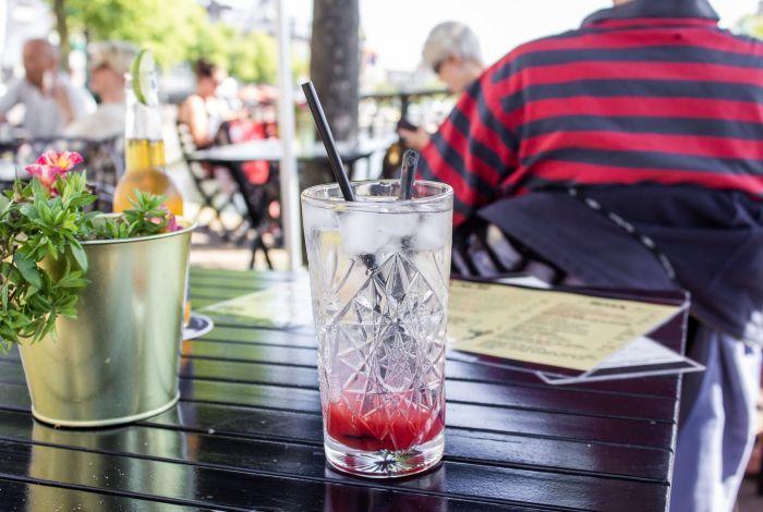 Menschen sitzen in einem Café-Außenbereich und genießen ihre Leckereien.