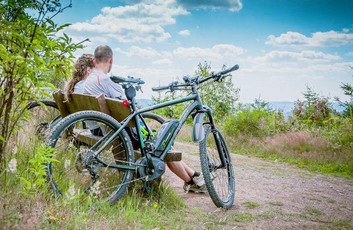 2 Leute auf einer Bank. E-Bikes daneben.