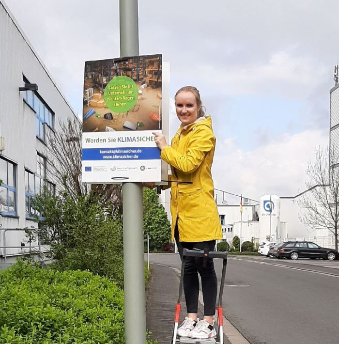 Junge Frau in gelber Jacke bringt Klimaschutz-Plakat an einem Laternenmast an
