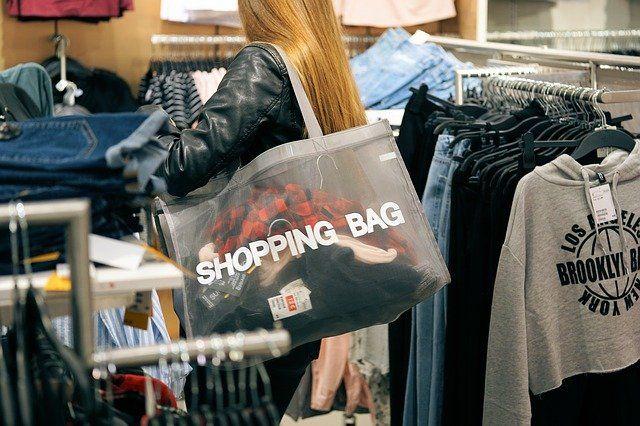 Junge Frau mit Enkaufstasche stöbert bei den Klamotten
