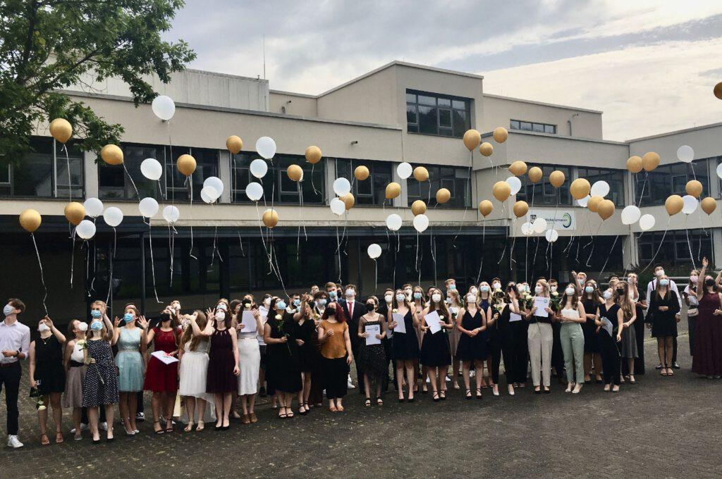großer Abiturientenjahrgang lässt weiße und goldfarbene Ballons steigen.