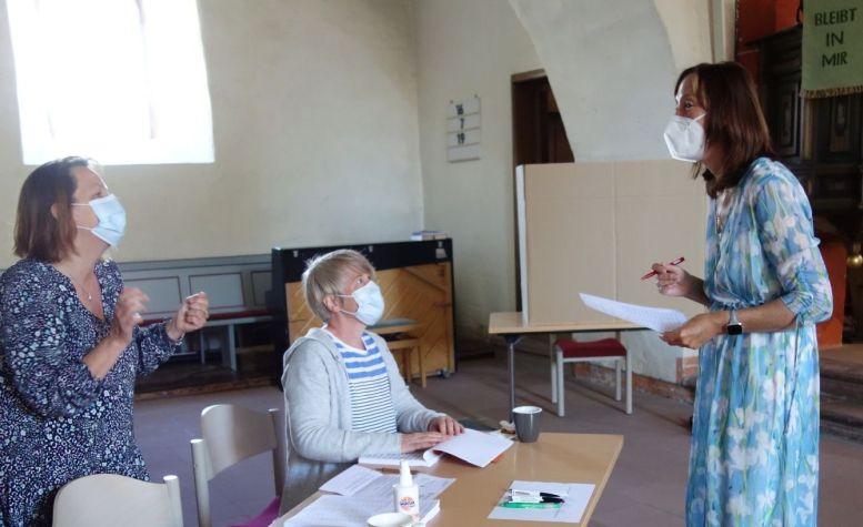3 Frauen mit Mundlappen in einer Kirche