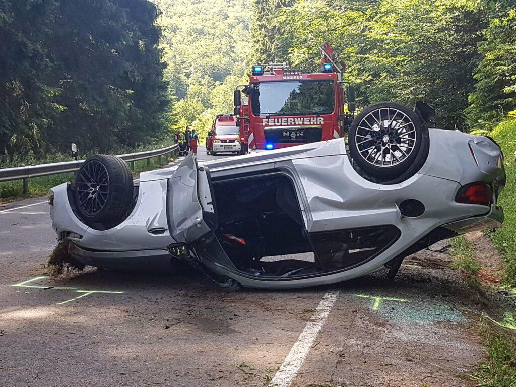 Unfallfahrzeug liegt auf der Straße auf dem Kopf.