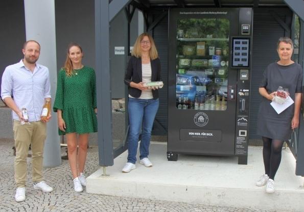 4 Leute vor einem Lebensmittel-Automaten