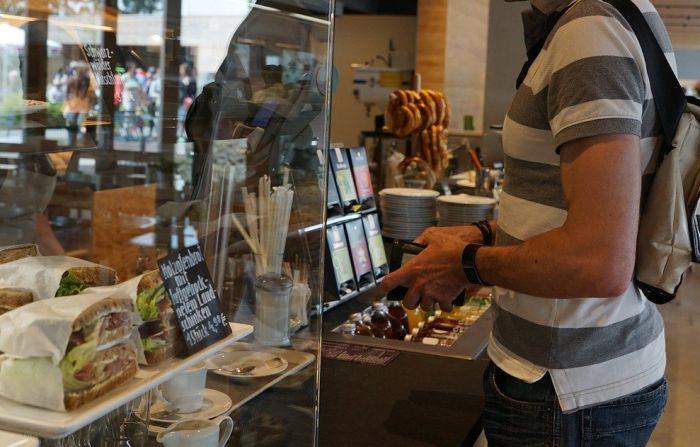 Mann in der Bäckerei. Geldbörse in der Hand.