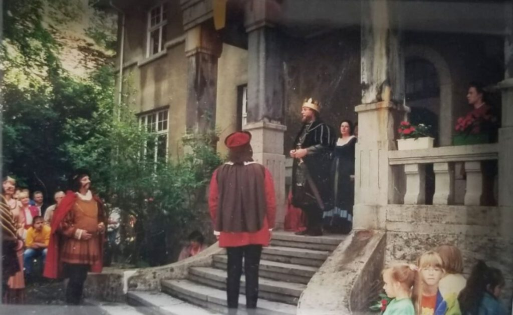 Historisch gewandete Menschen an einem Schloss