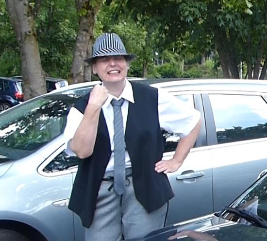Als Mann verkleidete Frau vor einem Auto