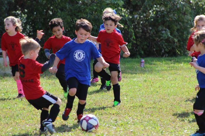 Kinder spielen Fußball auf dem Rasen