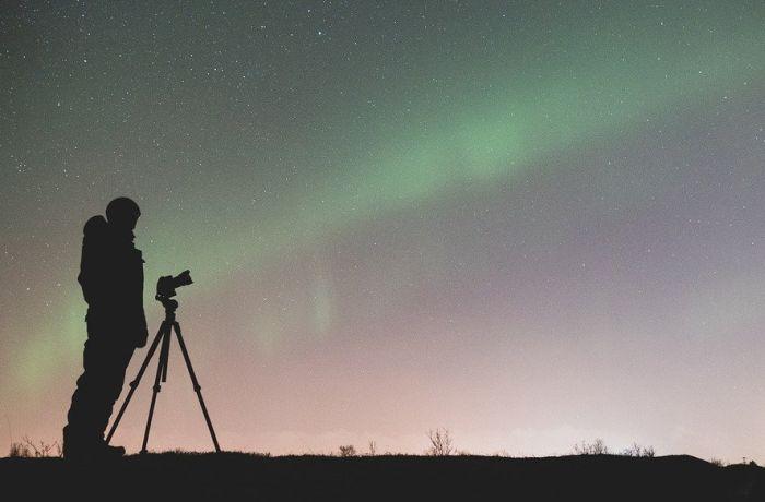 Schattenriss Mann vor Sternenhimmel und Polarlicht mit Kamera