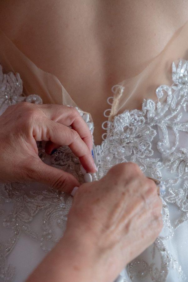 Mann knöpft Brautkleid zu. (Detailaufnahme)