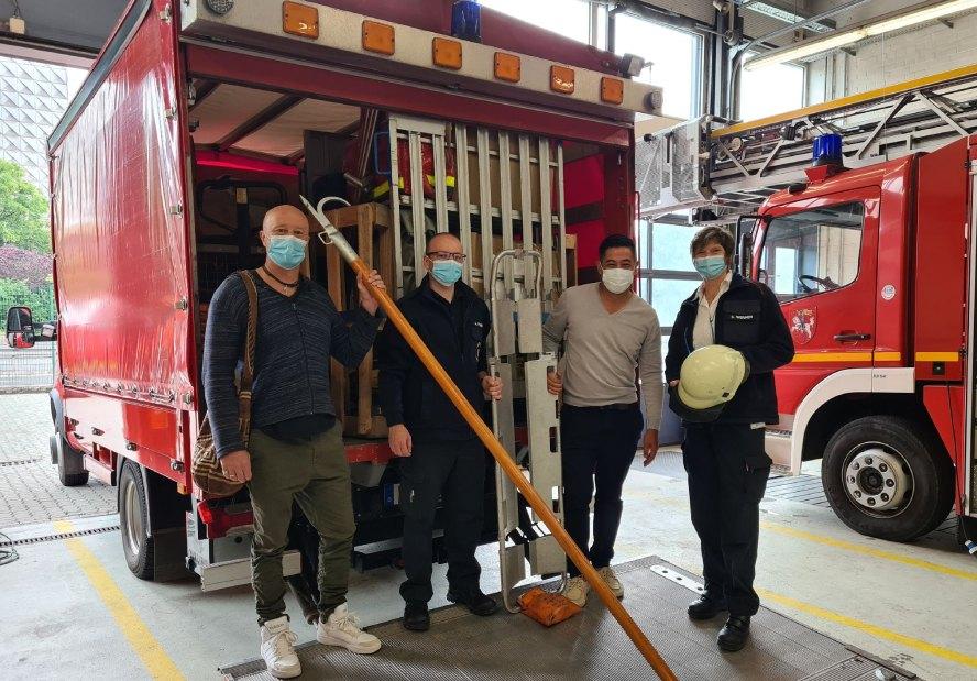 4 Leute mit Maske vor Feuerwehrfahrzeug