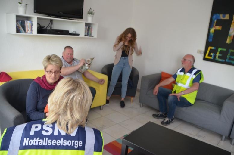 Menschen auf Sofas im Gespräch mit den Krisenmanagern