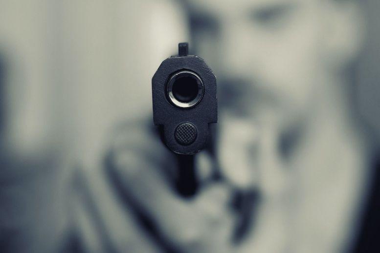 Mann schießt mit Handfeuerwaffe - direkt in die Kamera