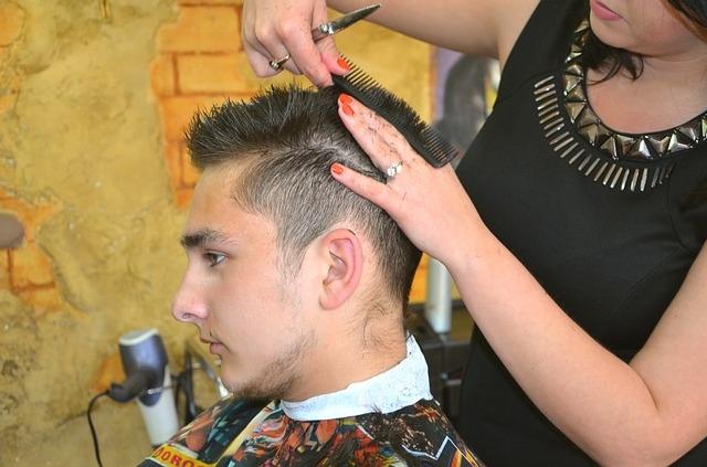 Friseurin schneidet jungem Mann die Haare