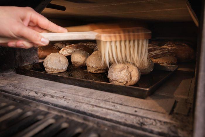 Brötchen werden im Backhaus-Ofen mit Wasser bestrichen