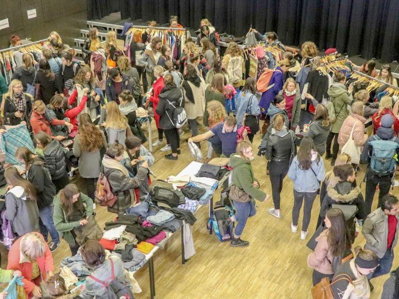 überwiegend junge Frauen beim Kleidertauschen in einem großen Saal