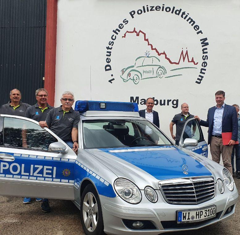 6 Offizielle bei einem Polizeioldtimer (Mercedes) vom Typ E280 CDI,