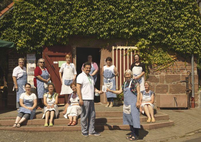 Gruppe Frauen vor einem alten Backhaus. Ein Mann übergibt eine Plakette.