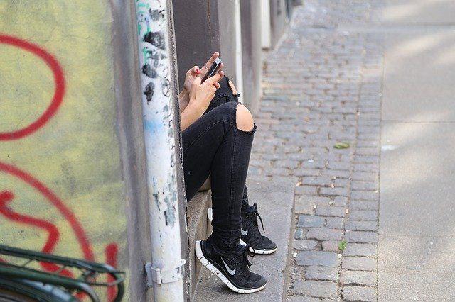 Teenager (nur die Beine sind zu sehen) in einem Hauseingang, Tippt am Handy herum.