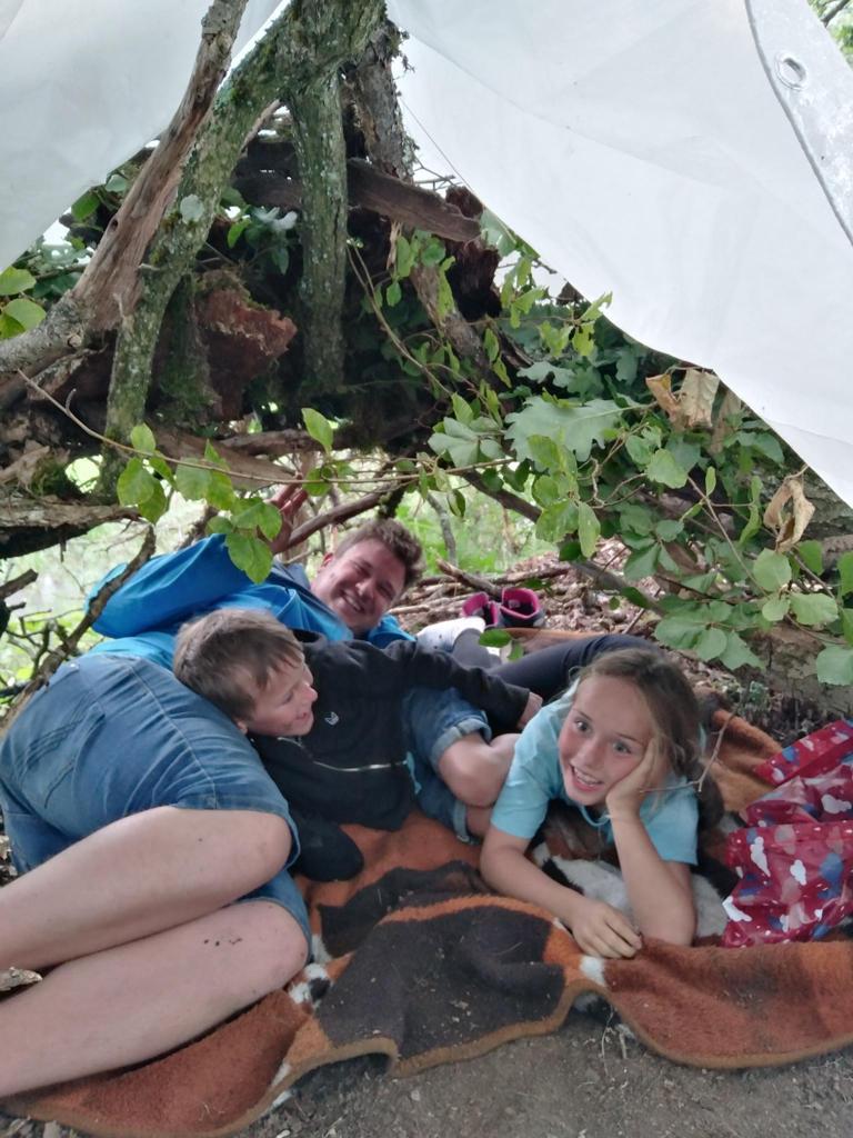 Helfer und 2 Kinder in selbstgebautem Zelt