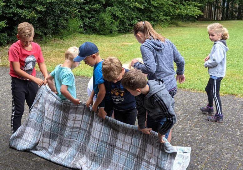 Kinder spielen mit einer Decke