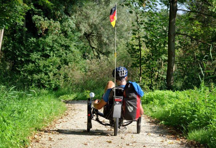 Mann fährt Liegerad auf einem Waldweg.